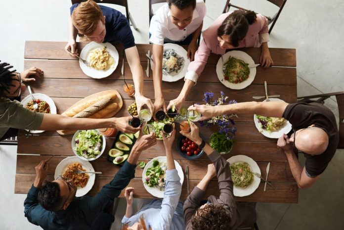 image of a group clinking glasses over a dinner table