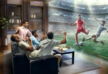 :biggrin:A group of young male friends are shocked while watching extremely realistic Soccer game on TV. They are sitting on a sofa in the modern living room faced to a real stadium with players instead of the front wall. It is evening outside the window.