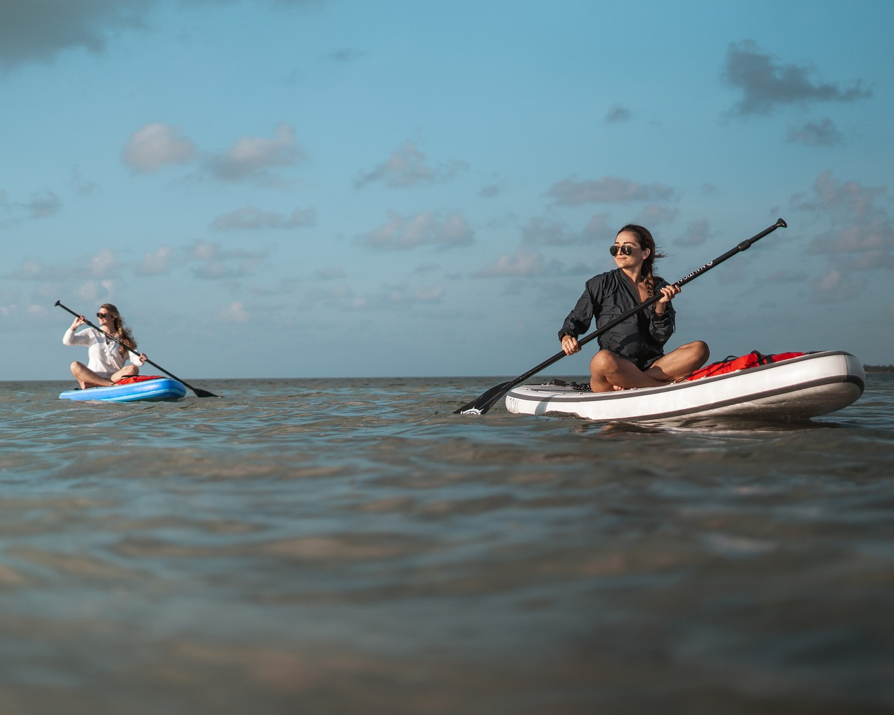 image of 2 women paddle boarding on the ocean