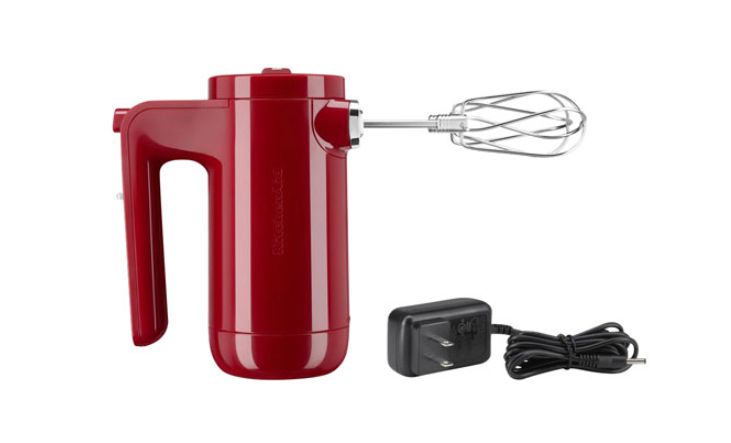 a cordless hand mixer next to its removable charging cable
