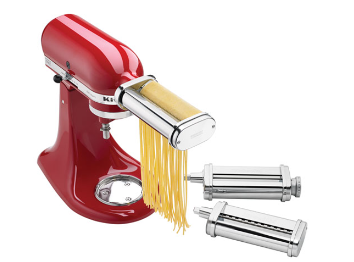 A KitchenAid stand mixer cutting fresh pasta with a pasta maker attachment