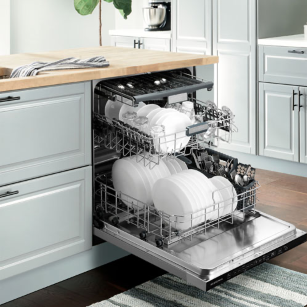 Insignia 24-inch dishwasher installed and open with dishes.